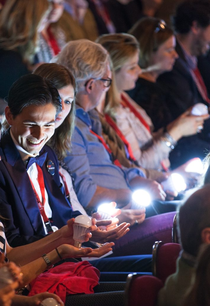 Social media content created live from your event can help reaching your target audience. At this TEDx event the audience is holding light bulbs.